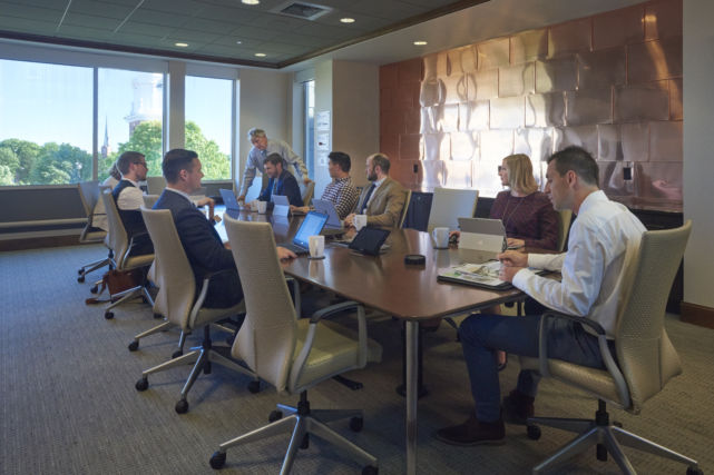 Business professionals around the table in new conference room